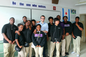 A group of students with the speaker in the center.